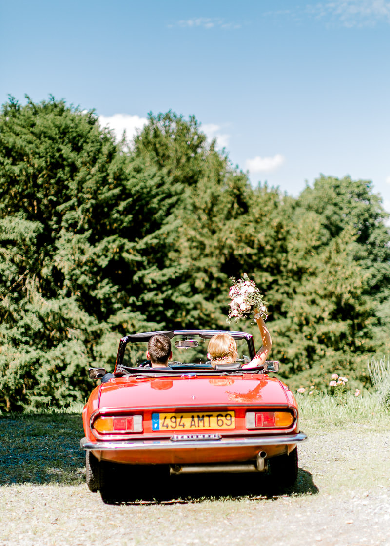 Couple de mariée dans triumph rouge en direction du domaine de la Genetière