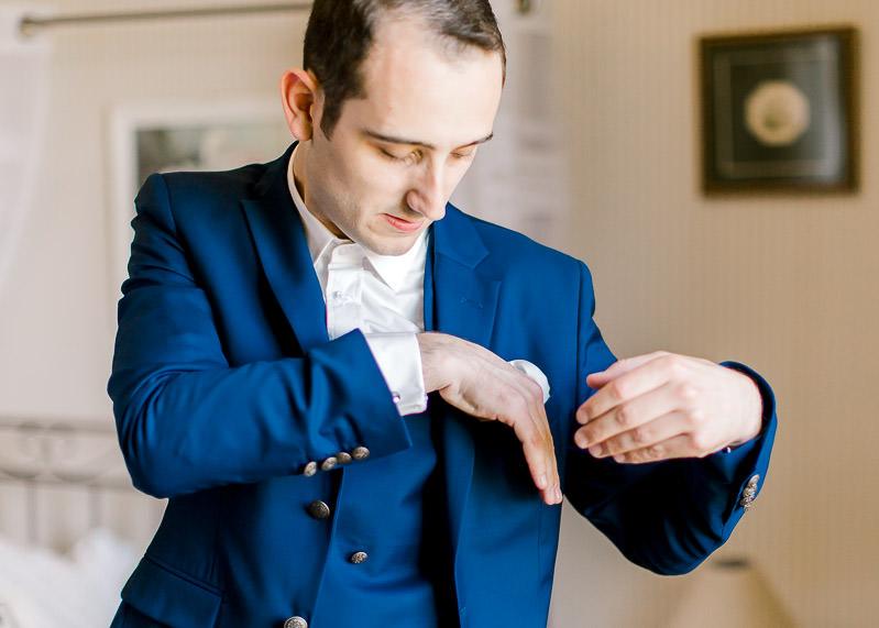 le marié ajuste la pochette de sa veste de costume