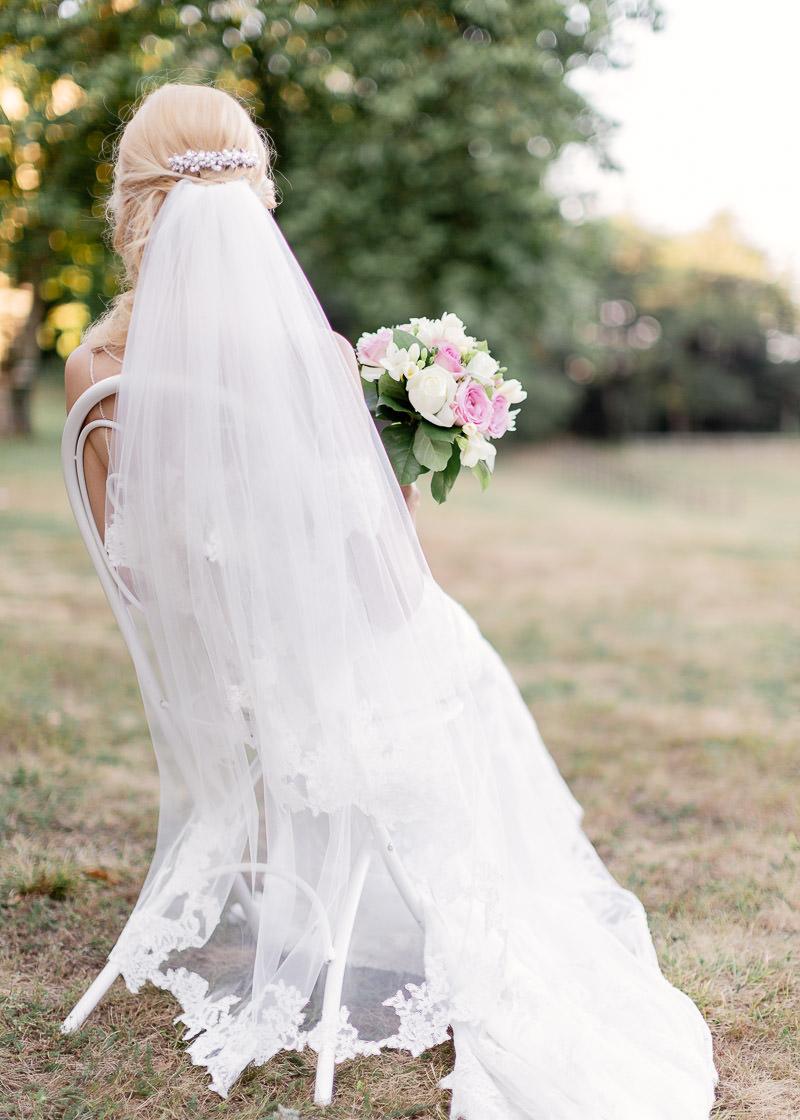 la mariée est assise et tient son bouquet de fleurs