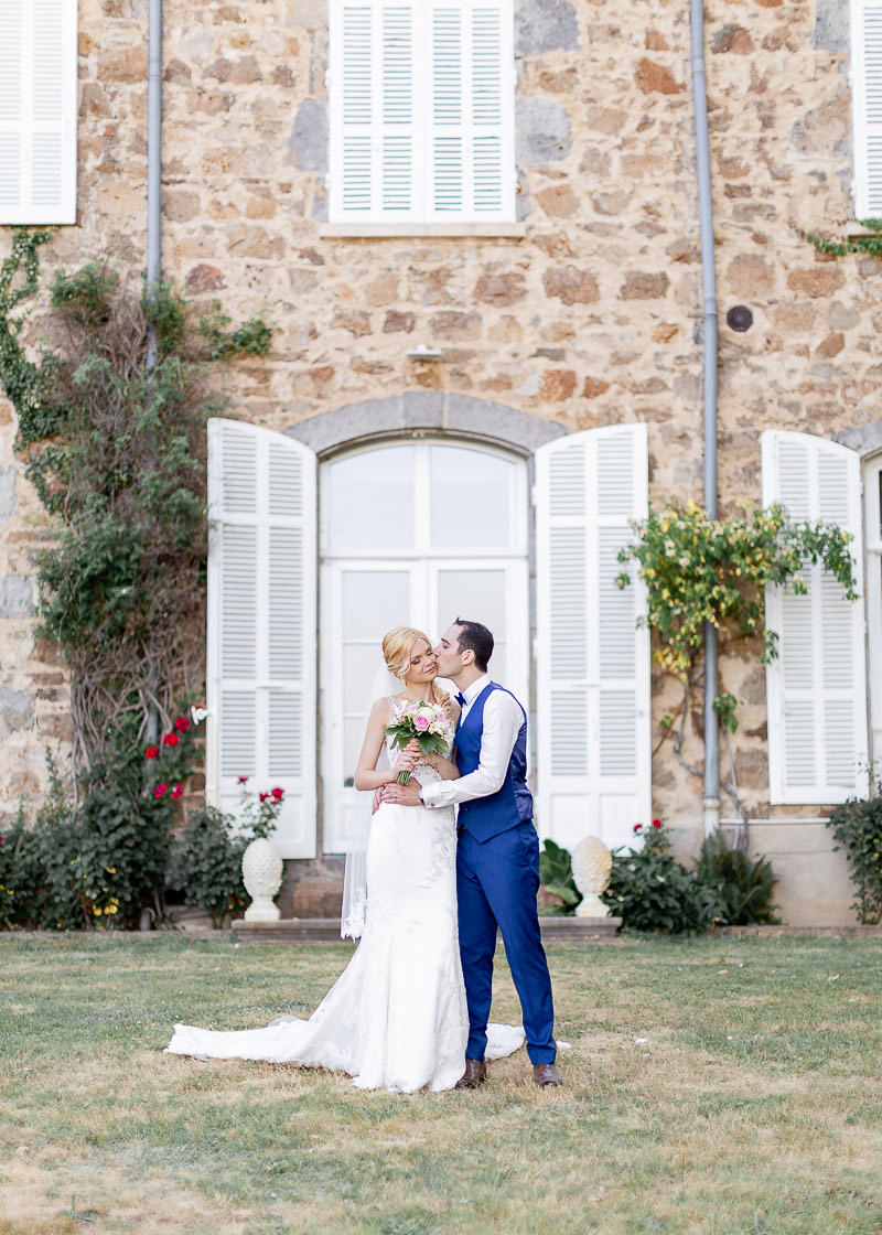 les mariés devant une grande fenêtre blanche
