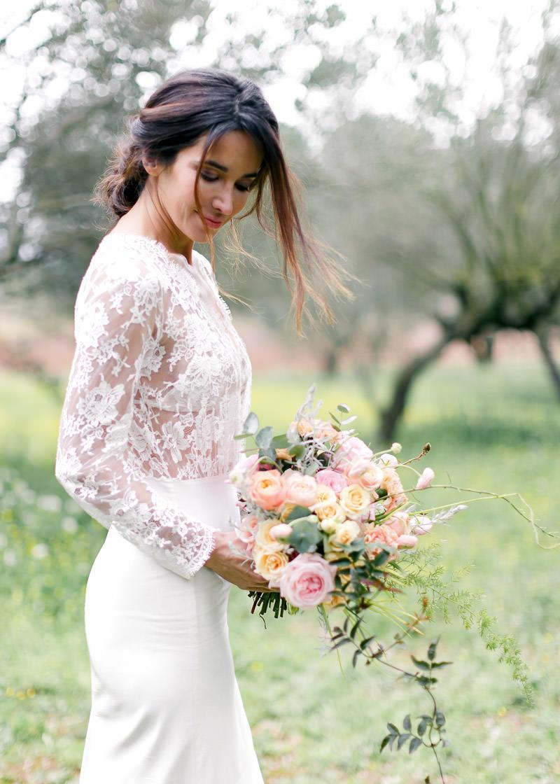 mariée avec sa robe en dentelle et son bouquet de fleurs