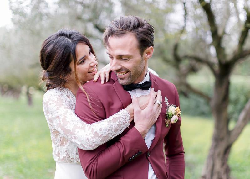 la mariée est derrière le marié et lui tiens la main