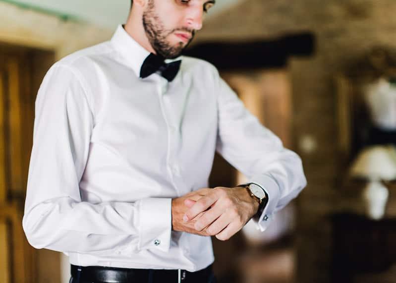 Le marié met sa montre au château du sou pendant les préparatifs