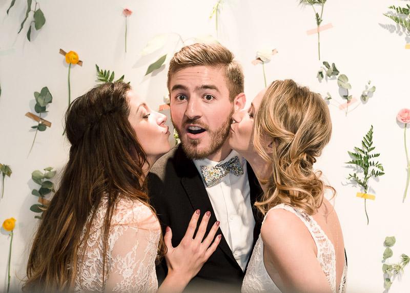 Deux mariées font une bise au marié