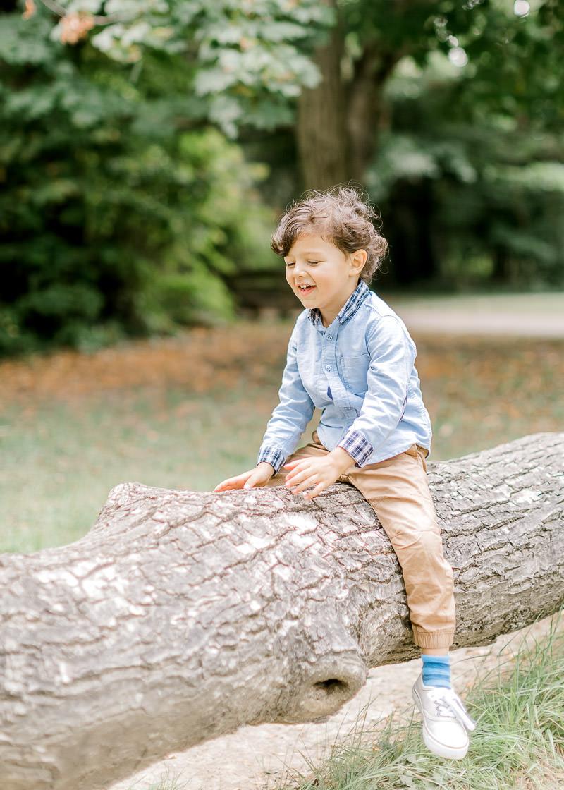 L'enfant est a cheval sur un tronc d'arbre dans le parc du Château de Rajat