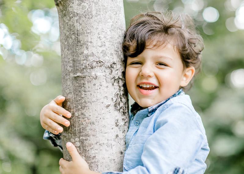 Un enfant s'accroche à l'arbre et rigole