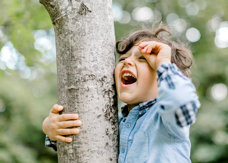 Enfant sur un arbre en train de rire pendant un shooting famille à Lyon