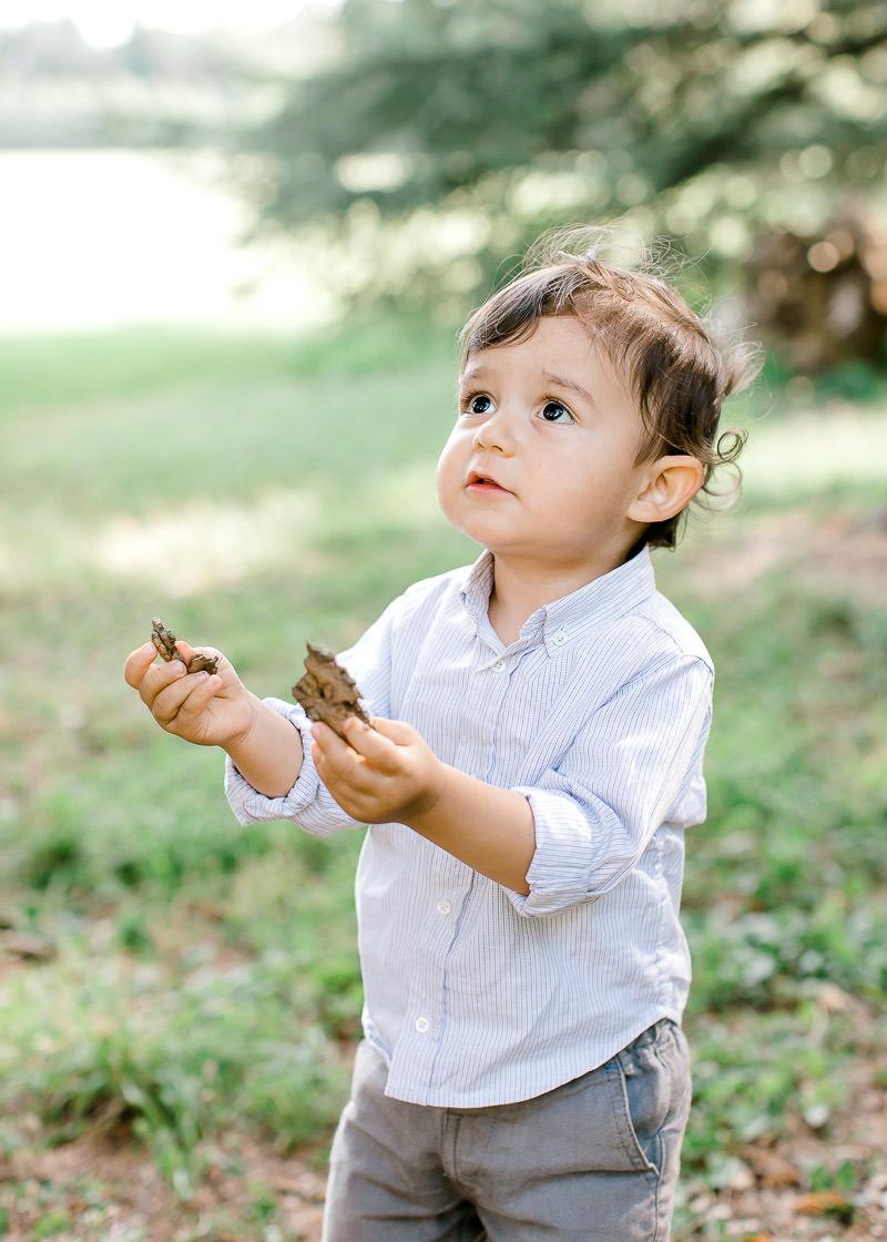 Séance photo Lyon - Un enfant regarde ces parents avec les mains pleine de feuilles