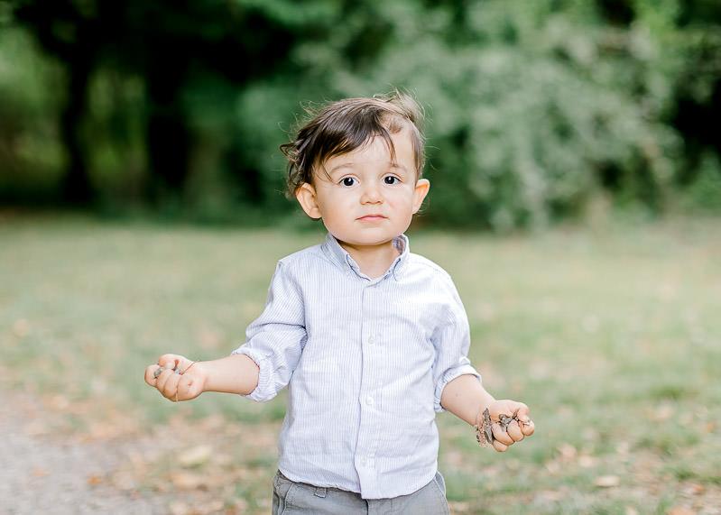 Un enfant regarde sa maman avec ces mains pleines de cailloux - Séance photo famille Lyon