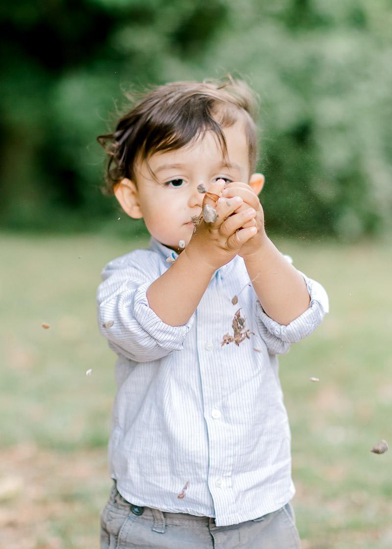 Un enfant joue avec des cailloux au château de rajat pendant une séance photo