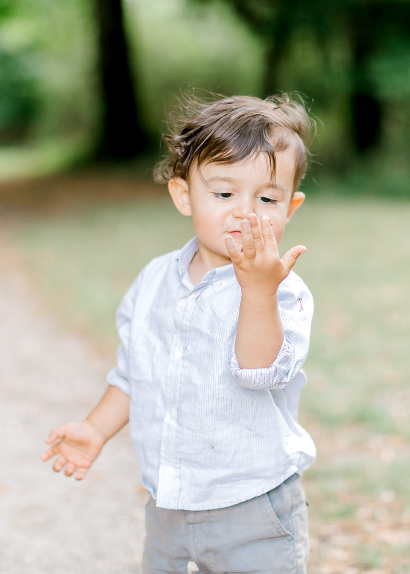 Un enfant joue avec des feuille et regarde ça main