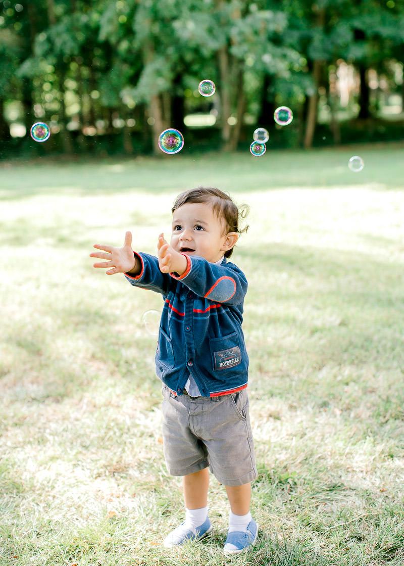 Un enfant essai d'attraper des bulles de savons
