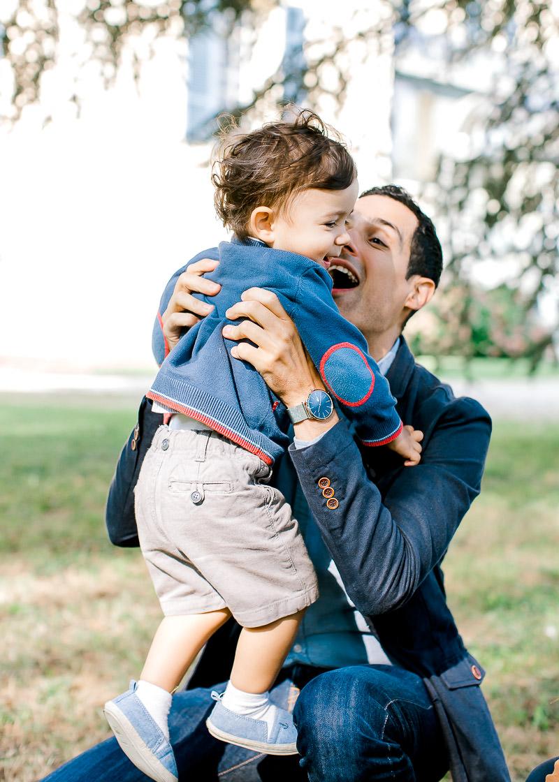 Un papa joue avec son fils et le prend dans les bras