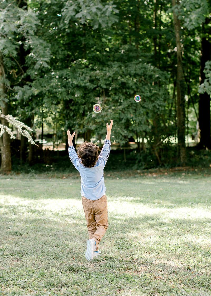Un enfant joue avec des bulles de savons. Parc du château de rajat