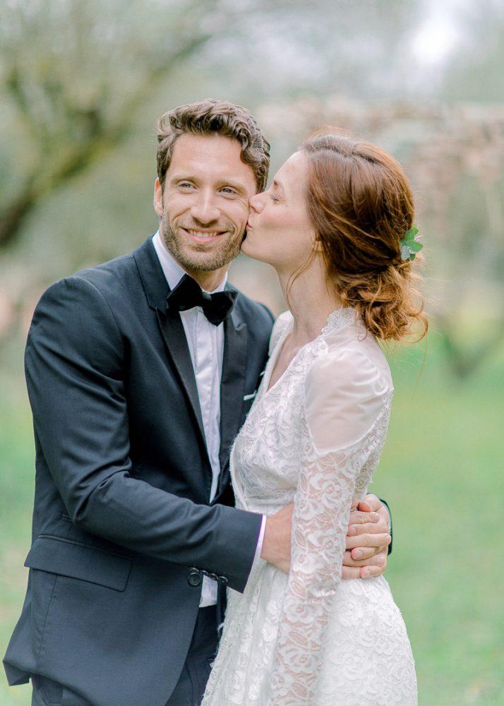 Couple de mariés en pleine nature, la mariés embrasse le marié