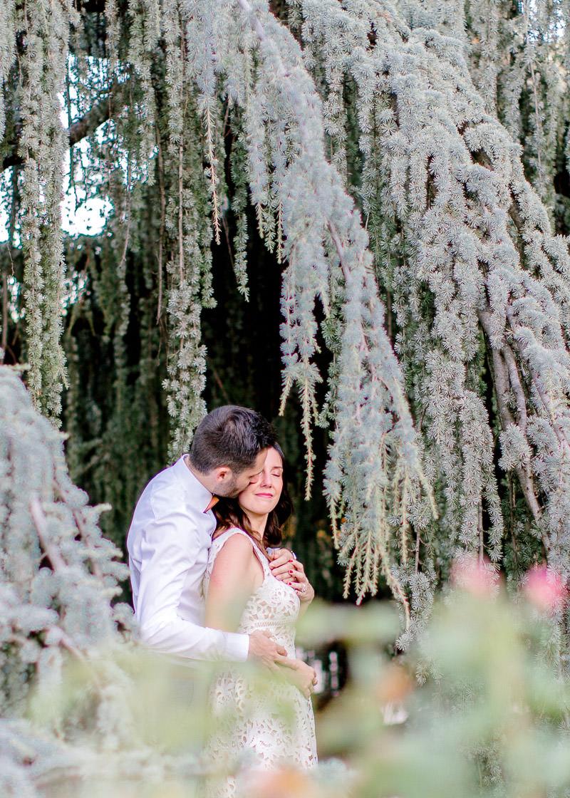 Le mari embrasse sa femme lors d'un shooting extérieur de couple