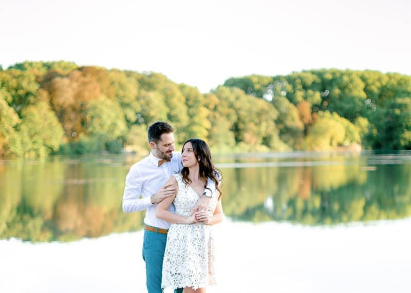 Un couple près d'un plan d'eau les bras dans les bras