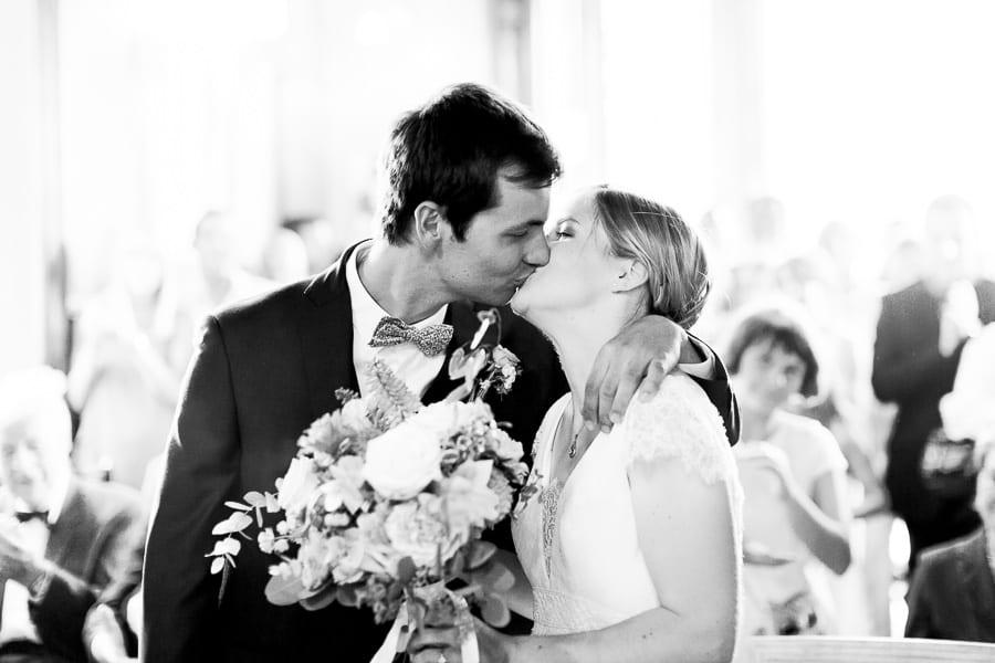 Le marié embrasse la mariée à la mairie