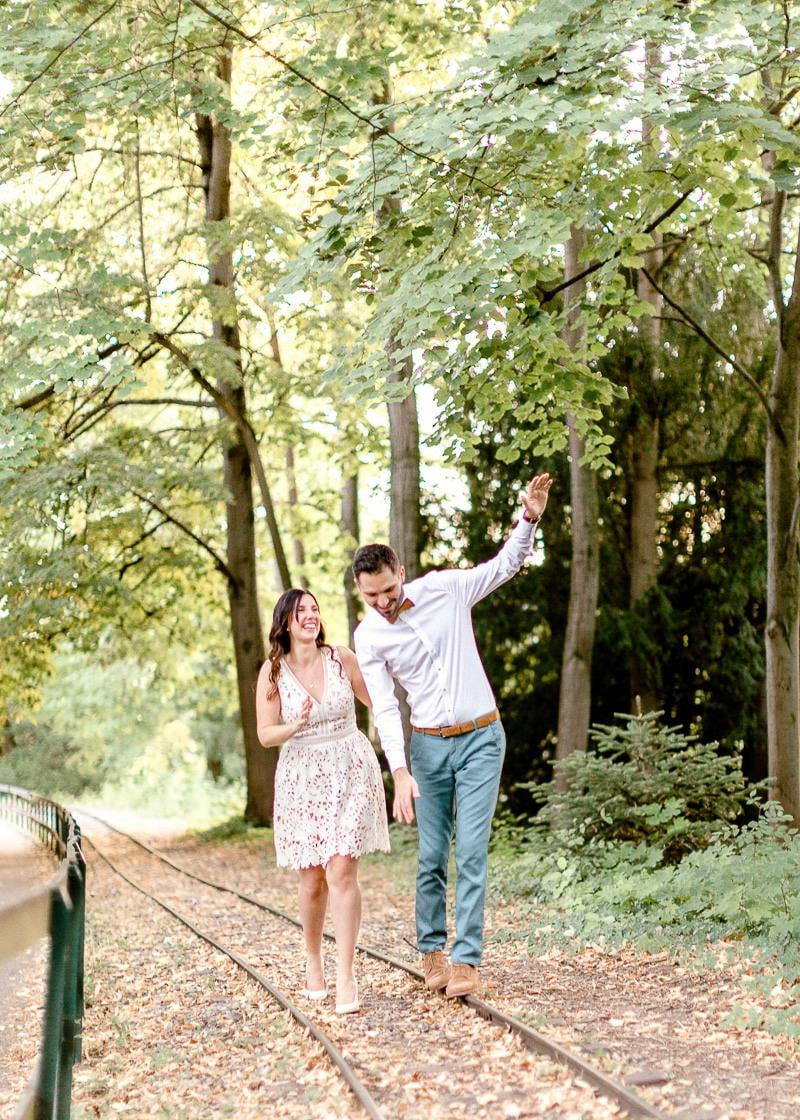 Un couple s'amuse a marcher sur une voie ferré desafecté